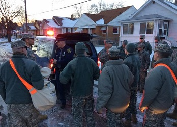 Michigan National Guard members go door to door to deliver water, filters, replacement cartridges and water test kits to residents of Flint, Michigan on January 19, 2016. (Photo by U.S. National Guard Maj. Joe Cannon)