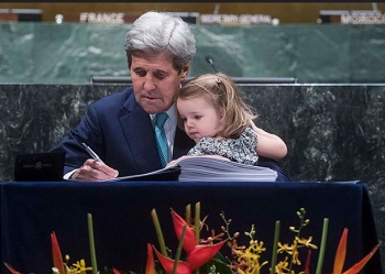 United States Secretary of State John Kerry, with grand-daughter in his arms, signs the Paris Agreement, April 22, 2016 (UN Photo by Amanda Voisard)